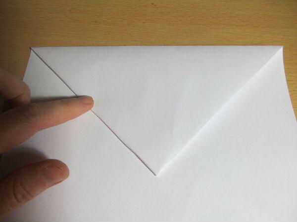 Полученный треугольник загибаем вниз фото